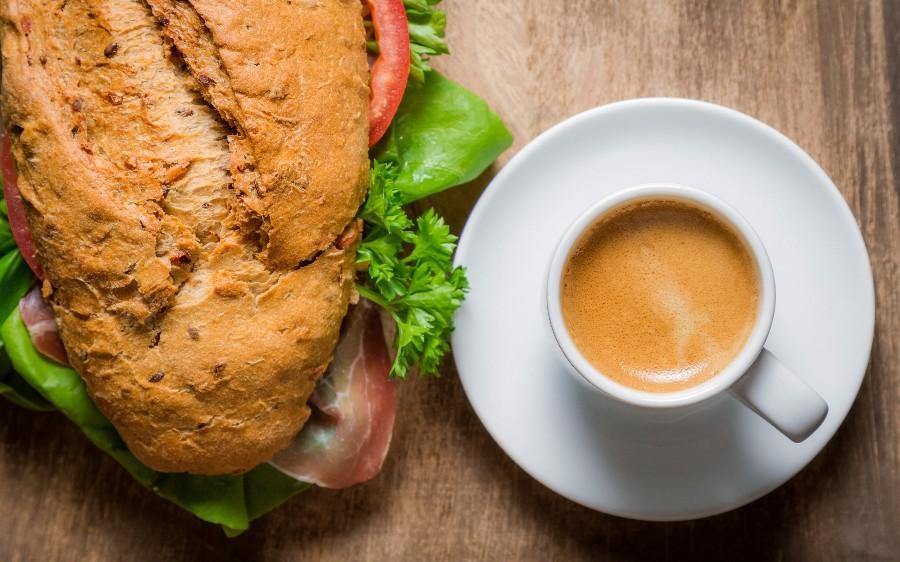 Большой сэндвич и чашка ароматного кофе